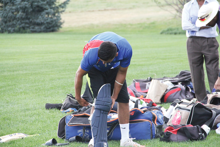 Jay Pathak of the Littleton Cricket Club straps on his pads during practice.