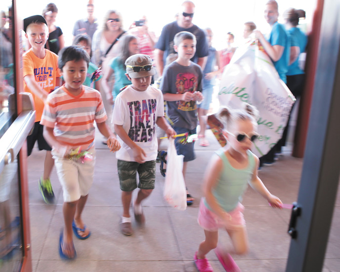 Kids charge the door of the new Lone Tree Library as confetti flies. The Lone Tree Library encompasses 25,000 square feet and houses a collection that is 40 percent larger than the building it replaced.