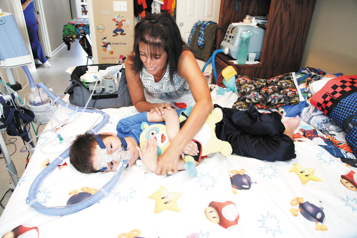 Lesa Rubino takes care of her son, Reece, who has spinal muscular atrophy and cannot sit up.