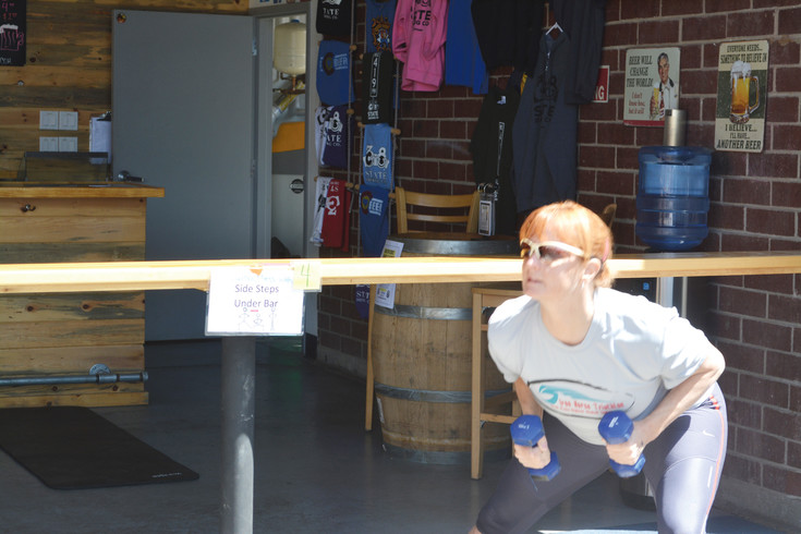 A counter at 38 State Brewing Company is used by Angie Mueting as a piece of makeshift workout equipment for Brewery Boot Camp.