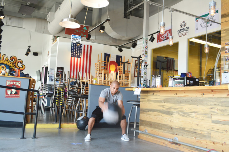 Martino Martinez of Highlands Ranch, a personal trainer with South Suburban Parks and Recreation District, slams a medicine ball to the ground at a Brewery Boot Camp workout.