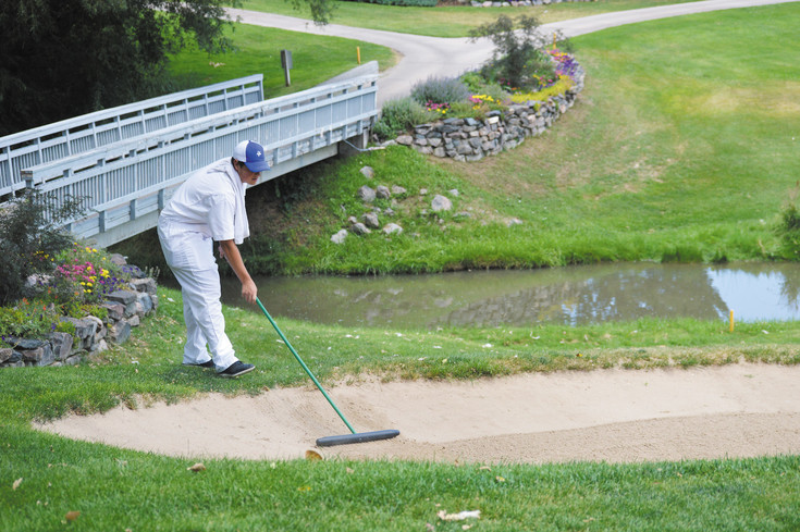 Nick Mayhan, a student at Mullen High School and a first-year caddie at Columbine County Club, smooths out the bunker near the tenth green at Columbine.