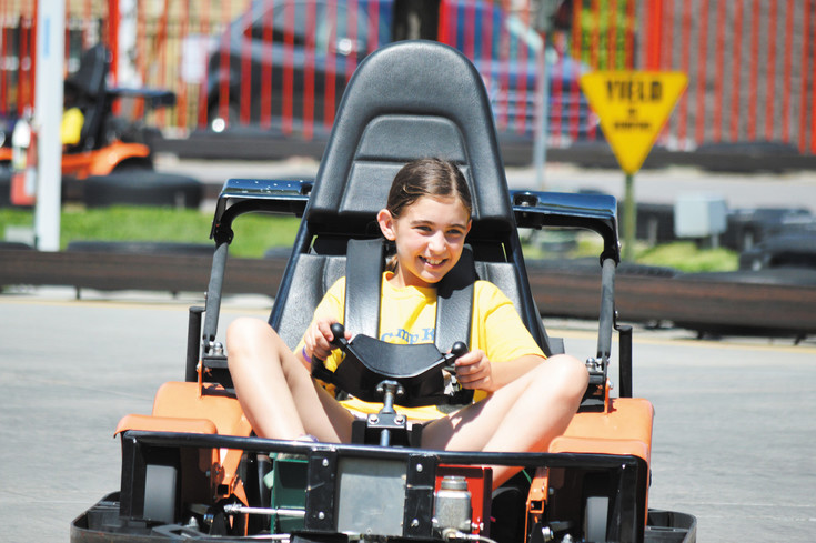 Elliot Staub can't contain her happiness as she weaves a go-kart along the track July 21 at Boondocks Food and Fun in Northglenn.