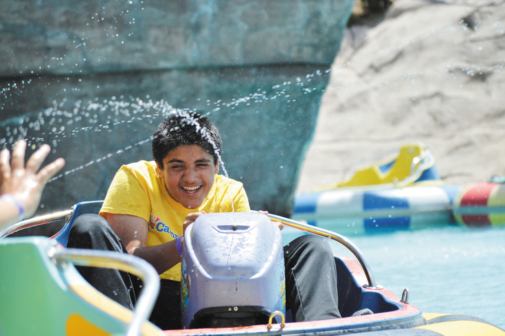 Nikhil, who had a healthy skepticism of strangers and didn't want to give his last name, engages in an act of kindness by helping cool down another camper riding the bumper boats at Boondocks in Northglenn.