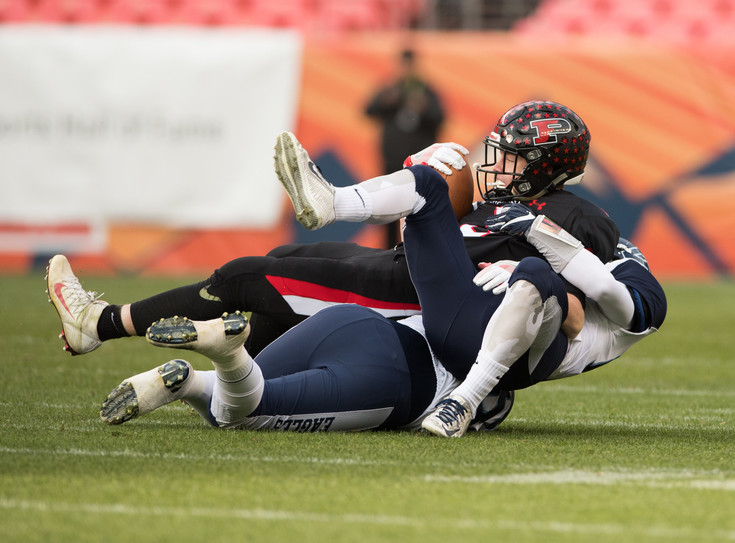 Pomona's Billy Pospisil (9) gets pulled to the ground by Valor Christian defenders Noah Kuzma (16) and Matthew Thibault (26).  The Eagles ended the day with the 30-14 victory in the 5A State Final at Sports Authority Field. Photo by Paul DiSalvo