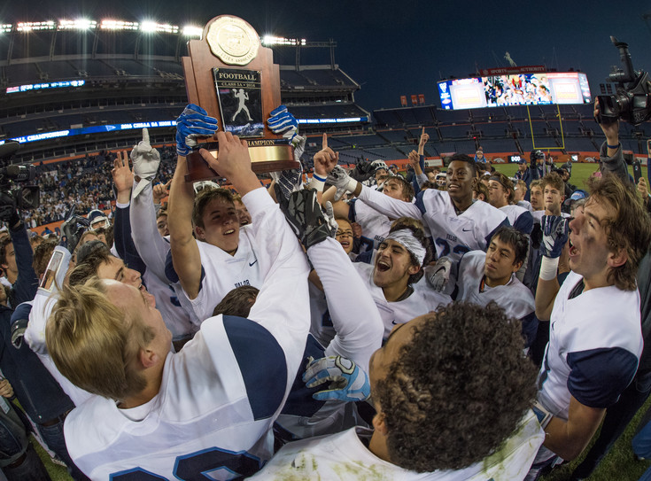 Valor Christian receiver Luke McCaffrey (2) and teammates raise the trophy as the Eagles ended the day with the 30-14 victory in the 5A State Final at Sports Authority Field. Photo by Paul DiSalvo