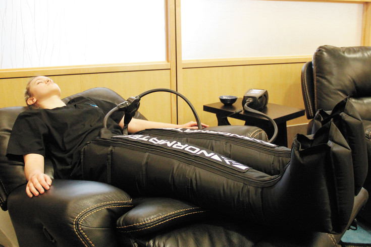 Venessa Kendall, lead technician at Innovative Body recovery in Meridian, uses a compression therapy machine on her legs at the clinic on Nov. 28. Kendall compares the machine, which uses air pressure to constrict parts of the body, to a deep tissue massage.