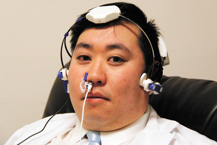Micah Kim shows off a brain therapy device at Innovative Body Recovery in Meridian on Nov. 28. The headgear directs infrared light into the brain to stimulate cells, and Kim claims it helps with conditions from autism to PTSD.