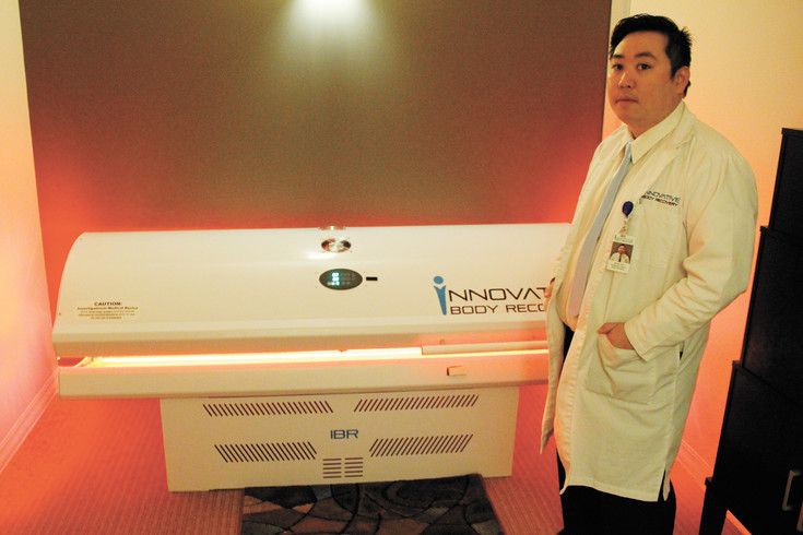Micah Kim, director of operations at Innovative Body Recovery in Meridian, demonstrates the clinic's whole-body light therapy machine. Kim says the treatments can regenerate cells in the body to treat hair loss and heal injuries more quickly.