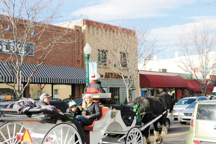 Arvada residents enjoy an old carriage ride around Olde Town Dec. 3 during the first of three Saturdays with Santa. Special events, a scenic streetscape and a vibrant mix of new businesses has seen Olde Town flourish in recent years.