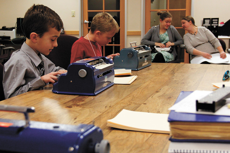 Students use Braille writers, devices similar to typewriters but designed to imprint paper with the Braille code, during the 2017 Braille challenge at the Colorado Center for the blind in Littleton. Pictured from left to right are Matthew Falco, 8, Asher Koren-Zoloto, 9, timekeeper Julie McGinnity and proctor Hindley Williams.