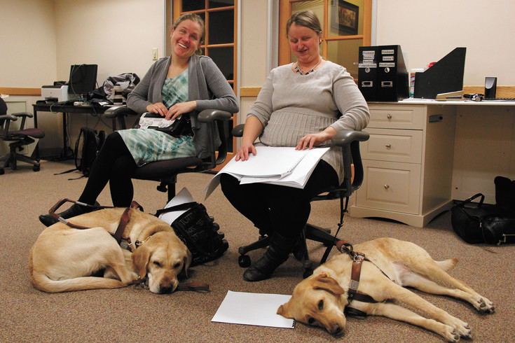 Julie McGinnity, left, and Hindley Williams and their companion dogs, Bill, left, and Delight, enjoy a break in the competition at the 2017 Braille Challenge at the Colorado Center for the Blind. Both women attend the career training program at the Littleton facility and volunteered to proctor the competition.