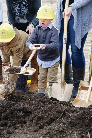Talon Lloyd, 3, shovels some dirt at the Hope House resource center ground breaking with his mom, Kendra Crispin, who is a Hope House graduate.
