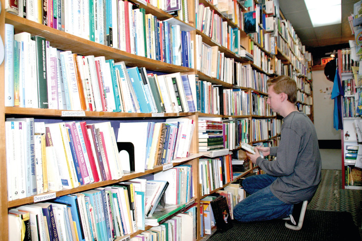 Dalton Geske, 18, of Denver shelves books at Christian Used Books, where he works part-time. The bookstore, at 3436 S. Broadway in Englewood, features 75,000 used books on site and 50,000 more stored in a warehouse.