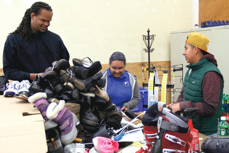 Parker residents Rashaad Short, left, Asi Sherril, center, and Ezequiel Jimenez, right, work their way through a pile of donations in the warehouse of the Goodwill Thrift Store in Parker.