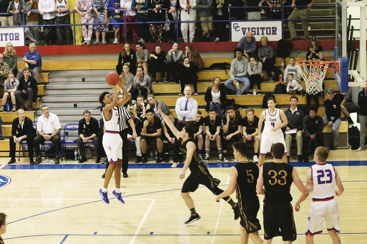 Dimitri Stanley puts up a jump shot for Cherry Creek as Arapahoe's Mitch Sweeney moves in to defend during the Feb. 8 league boys basketball game at Cherry Creek High School. The Bruins were leading after three quarters but the Warriors scored 23 fourth period points and won, 67-63.