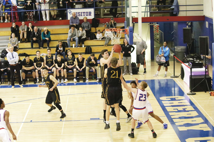 Arapahoe's Ben Timmons pulls down a defensive rebound during the Feb. 8 league basketball game against Cherry Creek.  Timmons scored 11 points, led the team in rebounding with nine and blocked two shots as the Warriors won the rivalry game 67-63.