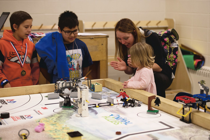 Ezekiel Maestas, left, and Damon Aguilar watch their robot successfully perform its task with task with Jennifer Rizzo and her daughter. The robot is programmed to push a shark tank from one end of the table to the other without tipping it. The tank must also end within a square template on the table.