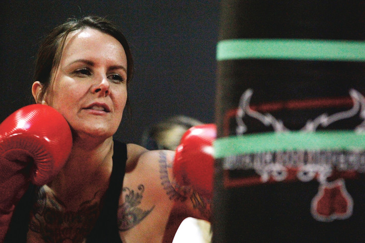 Ali Daily works out her frustrations during a workout session at iLoveKickboxing in Parker. On the eve of Valentine's Day, the gym hosted its Shred Your Ex event in which attendees beat up on photos of their exes.