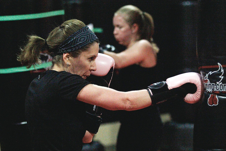 Kathy Alpin, front, puts her gloves to work on a heavy bag at Parker's iLoveKickboxing on Feb. 13. The Shred Your Ex event featured black outfits, loud music and photos of participants' exes taped to punching bags.