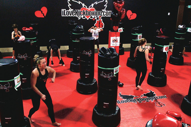 Participants at iLoveKickboxing's Shred Your Ex event warm up before kicking and punching photos and printouts of the people and concepts that frustrate them. The hourlong class features pounding music and a rigorous workout.
