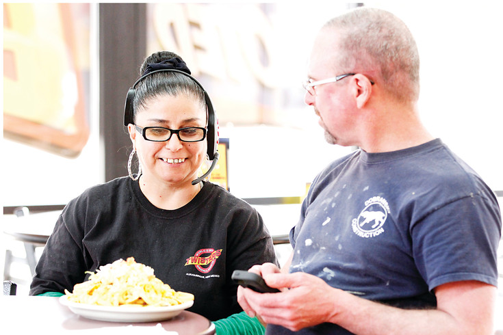 Jennie Redman, an Aurora resident who commutes to her job at Twisters Burritos and Burgers in Parker, serves chile fries to customer Jim Gatzke, also of Aurora. Store manager Gary Hatfield has had problems finding applicants to fill vacant positions at the store.