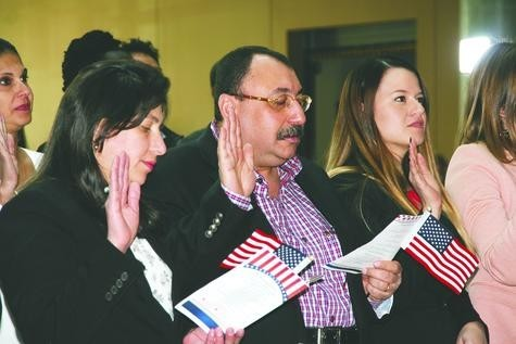 On the left, Norma and Youssef Ibrahim — along with 50 other immigrants — take the Oath of Allegiance to the United States as new American citizens during a naturalization ceremony Feb. 14 at the History Colorado Center. The Ibrahims left their careers as doctors in Egypt to come to the U.S. so they could provide a better life and a good education for their three children.