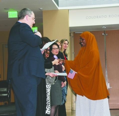 "On the right, Hamdi Ahmed, 28, of Greeley holds her mini American flag and shakes hands with representatives from U.S. Citizenship and Immigration Services (USCIS), elected officials and the History Colorado Center as she receives her Certificate of Naturalization on Feb. 14. Ahmed, originally from Somalia, said she is ""so happy"" to now be a U.S. citizen because it something she has always dreamed about."