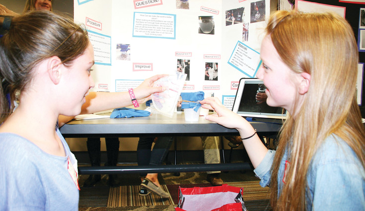 Bell Middle School students Morgan Brodnax, 12, and Sasha Bandock, 13, set up their salt water filtration device at the Girls in STEM competition on Feb. 22 at the Golden Library. About 50 girls entered the competition, and 18 projects were presented at the competition.