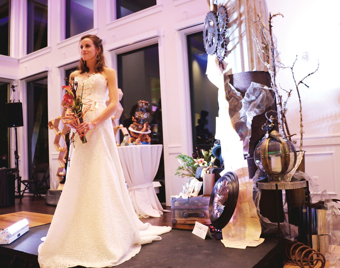 Katie Miller wears a bridal gown from Compleat Couture, a charitable bridal salon at 7562 South University Blvd., Centennial. The theme of her stand is steampunk, a style design that mixes historical industrial with modern technology.