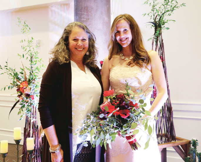 Maxine Cutts Alcott, owner of Abloom Inc., a floral shop in Highlands Ranch at 9325 Dorchester St., stands next to Compleat Couture model Brittany Johnson, who is holding a bouquet designed and donated by Alcott.