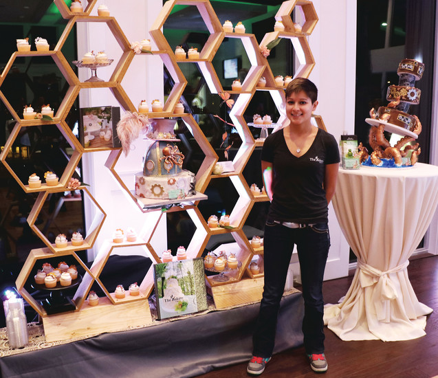"Ashley Mora, party host of The Makery, a cake shop at 8203 South Holly St., Centennial, displays her cupcakes in a giant honeycomb at the Colorado Un-Bridal Show. ""We like the idea of the different themes and styles,"" said Mora, who was one of many vendors who donated their services."