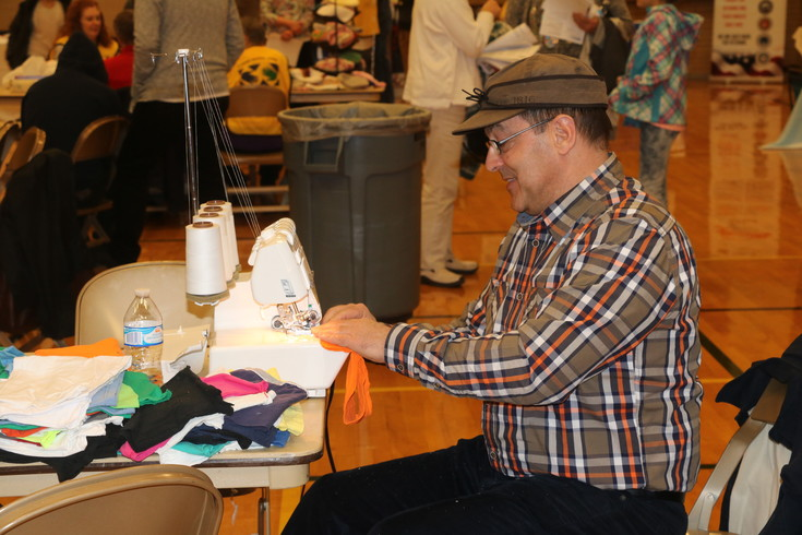 Scott Pexton, a volunteer from the Church of Jesus Christ of Latter-day Saints, works on sewing a hat for children as part of the first Just Serve Volunteer Fair on Feb. 25.