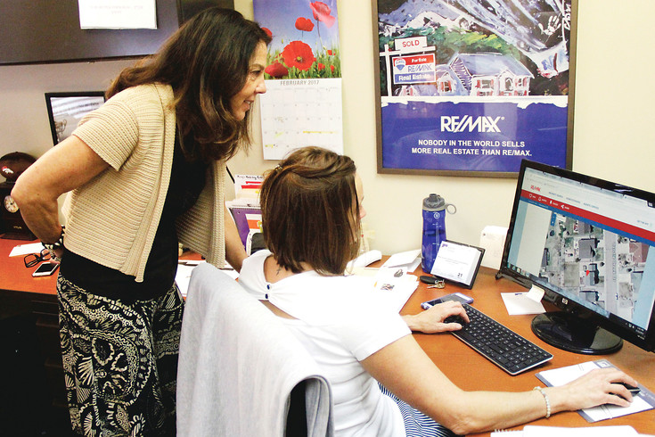Realtor Sandi Zimmerman and her assistant Milissa Duckworth look at local home prices in her Castle Rock office. Zimmerman says she has to advise some clients to look outside of their preferred area and be ready to view a house at a moment's notice to get their offers in.