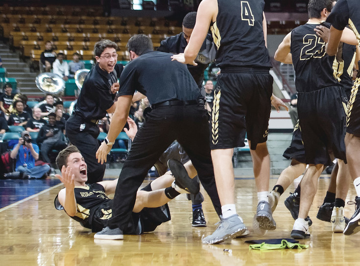 Coaches and teammates surround Rock Canyon's Nick Janedis as he falls to the floor in joy after hitting the last second tip-in to give the Jaguars the 42-40 win in the Great 8 on March 4 at the Denver Coliseum.