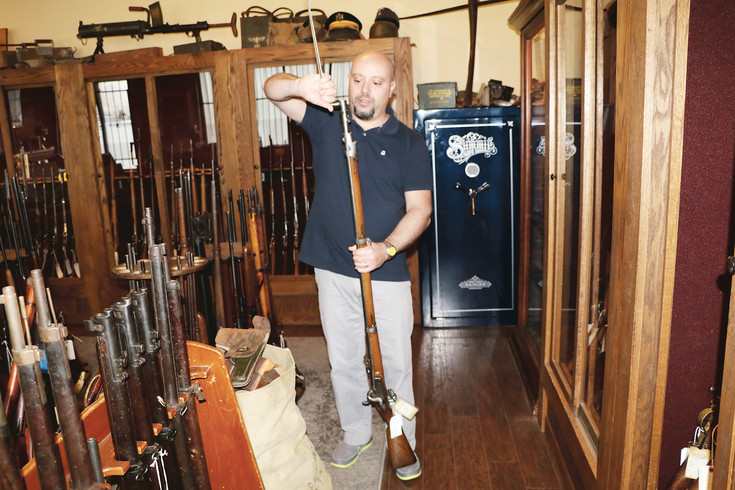 Giovanni Galeano, who owns the recently opened Old Steel antique weapons and military memorabilia shop in Englewood, folds out the bayonet on an 1850s Swiss muzzle-loading military rifle. The store carries weapons dating from before the Civil War to the modern area. There are guns, knives and swords as well as a large collection of medals, insignias and other military memorabilia.