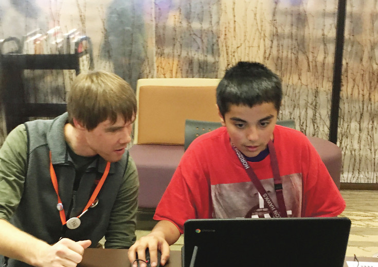 Jakob Seelig watches as  Joseph McGarvey races to connect to two Wikipedia entries with the fewest number of mouse clicks, part of Anythink Library's Wikipedia racing Feb. 28 in Thornton.