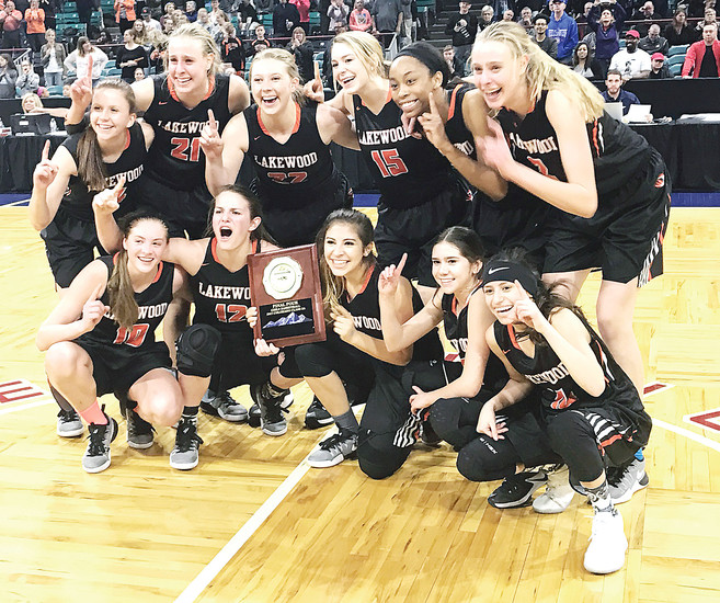 Lakewood's girls basketball team poses at center court at the Denver Coliseum after the Tigers defeated top-seed Highlands Ranch 61-49 in the Class 5A state tournament quarterfinals March 3.