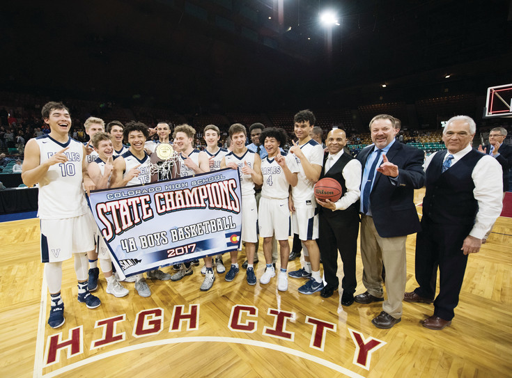 The Valor Christian boys basketball team holds up its state championship banner and trophy to celebrate the 68-55 victory over Lewis-Palmer March 11 at the Denver Coliseum.