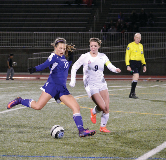 Littleton junior midfielder Katie Puchino kicks the ball away from Chaparral's Eliot Edwards during the season-opening soccer game on March 9 at Echo Park Automotive Stadium in Parker. Edwards scored twice as the Wolverines notched a 4-1 win over the Lions.