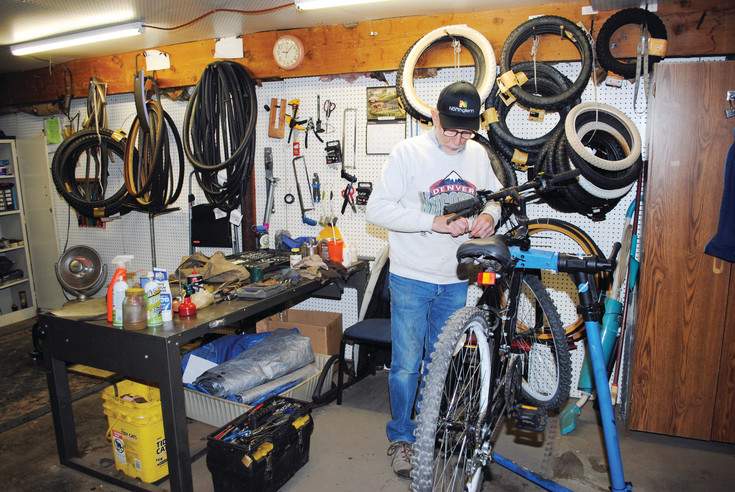 Jerry Gavette fixes a brake cable on a bike.  He uses a professional bike stand to make the repairs easier.