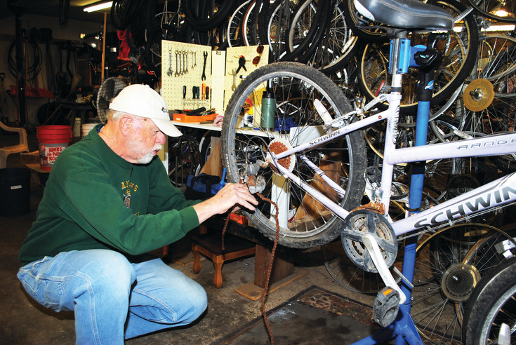 Don Skinner removes a rusted chain from a bike; extra wheels hang on the shop wall behind him.