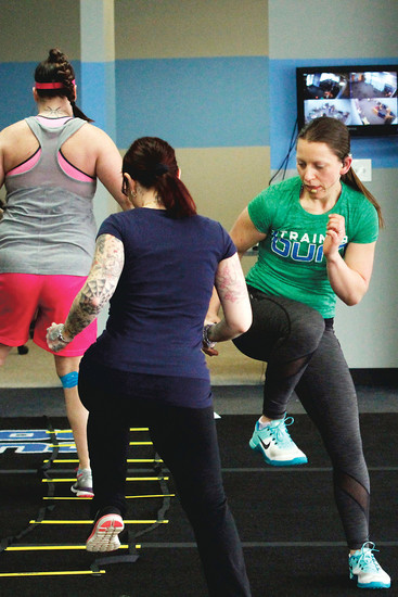 Sarah Ragatz, right, works out alongside her clients during a 30-minute camp at the Burn Boot Camp gym in Parker. Each member of the gym meets one-on-one with Ragatz or another trainer to outline personal goals and discuss how nutrition and exercise combine to meet those goals.