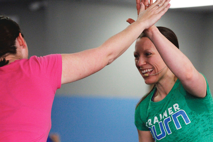 Sarah Ragatz, right, celebrates with a client during a workout in the gym she opened with her husband, Carman Ragatz. Ragatz handles the training sessions and social media responsibilities and Carman manages the bookkeeping and administration at Parker's Burn Boot Camp.