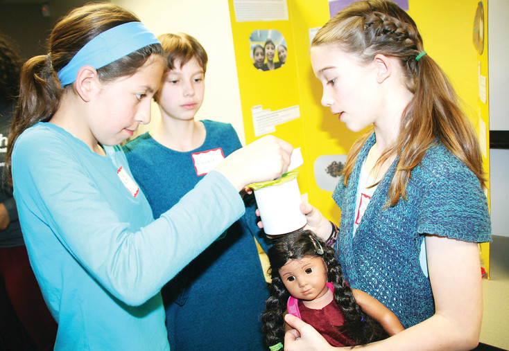 "From left, Lillian Bestor, 11, Kit Arbuckle, 11, and Annika Waples, 11, pour dirty water into a clean water filtration system that they made for the Girls in STEM competition. The inspiration for the project was a book called ""A Long Walk to Water"" by Linda Sue Park, in which the girls learned of the difficulty that some people in Sudan face when it comes to accessing clean drinking water. Their project won an honorable mention at the March 8 Women's Day event."