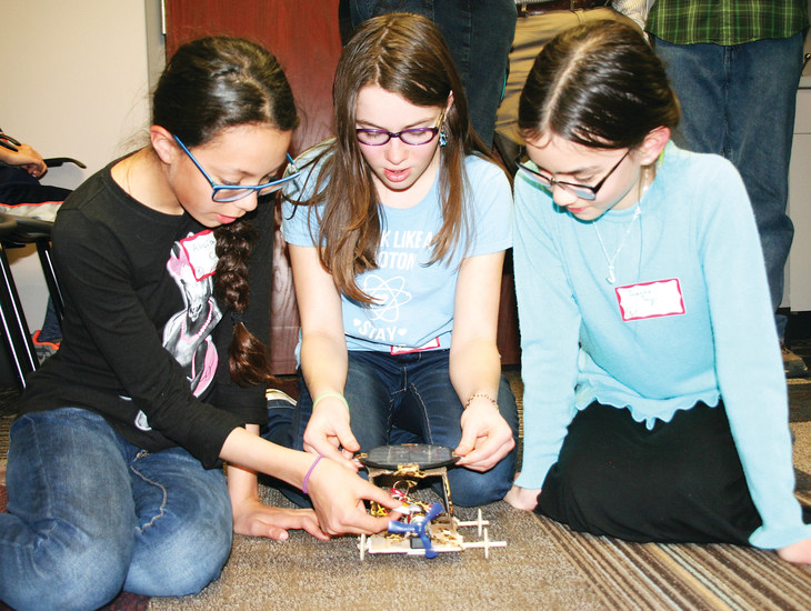 Alicia Crespin, 12, Jacqueline Rossell-Rust, 12, and Joanna Toy, 11, put their solar-powered car to the test at the Girls in STEM competition on Feb. 22 at the Golden Library. It took the girls about a month and a half to complete the project. Their work included research, brainstorming, planning, building the car and a number of rounds of evaluation, the girls said.