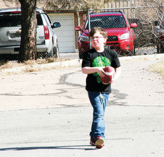Matthew Eagleton, 8, a third grader at Pleasant View Elementary School in Golden, carries a football during recess on a sunny day in early spring. At the end of this school year, Pleasant View will close and the students will have to adapt to a new school community.