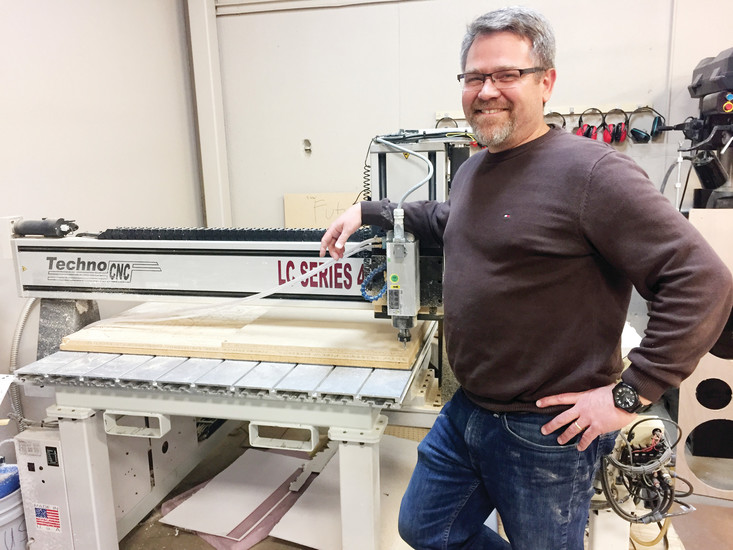 Mike Shallenberger, department chair of engineering at STEM School and Academy, stands next to a CNC — Computer Numeric Control — machine that cuts a variety of materials. His class is currently using the machine to create a Chinese checker board.