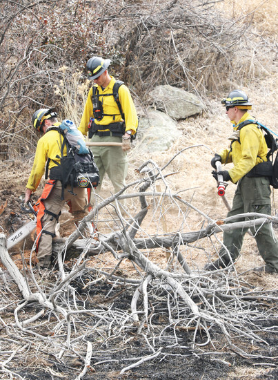 Firefighters work to root out hot spots on the slopes of South Table Mountain on March 10, using chain saws and rakes to break up troublesome fuel sources, and water hoses to put out smoldering spots.