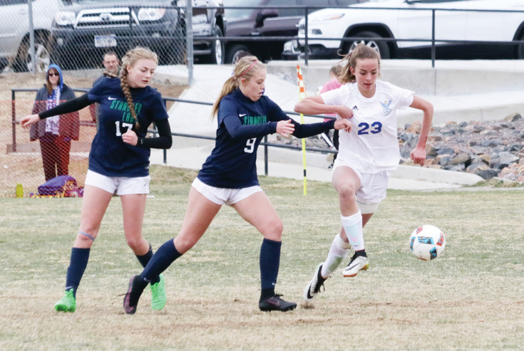 Skylar McNulty pushes the ball up the field for Highlands Ranch as Shannon Patrick (9) moves in to try to cut off the move during the March 11 girls soccer game. The game remained scoreless until deep in the second half when Sophia Shepherd scored as the Falcon won the game, 1-0.